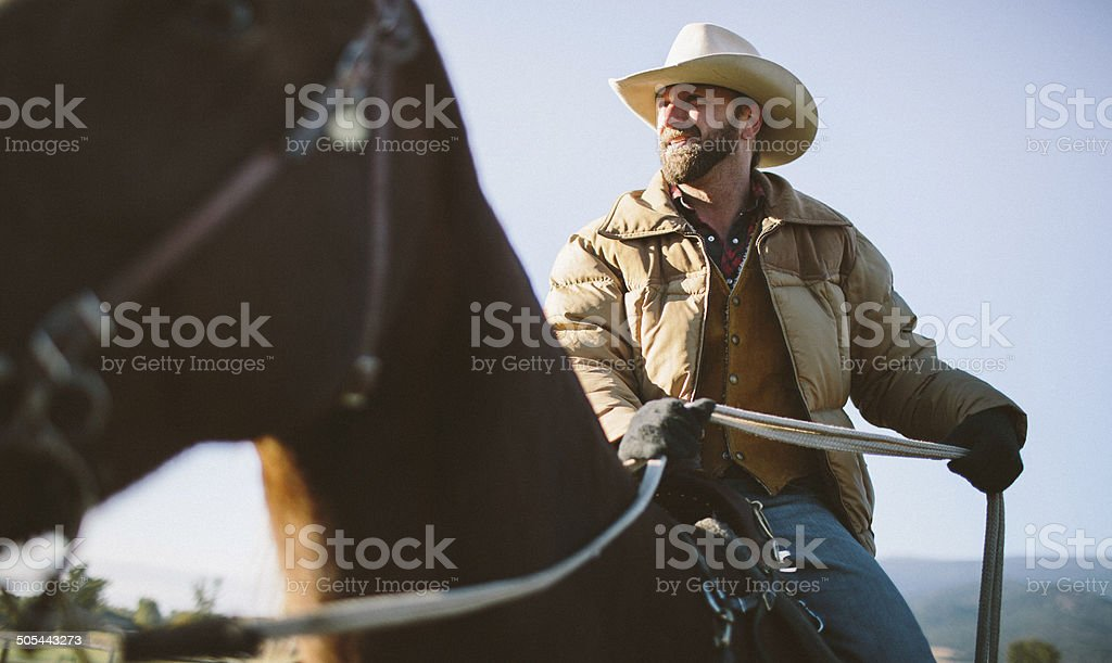 Close-up  of cowboy riding horseback with mountains behind royalty-free stock photo