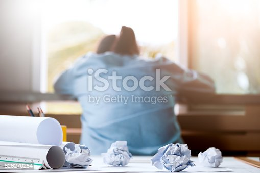 istock Close-up of crumpled paper on table with unhappy businesswoman was frustrated. Concept of no idea to thinking 828270284
