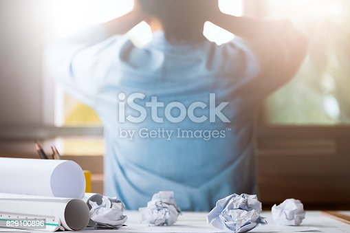 istock Close-up of crumpled paper on table with unhappy businesswoman was frustrated. Concept of no idea to thinking 829100896