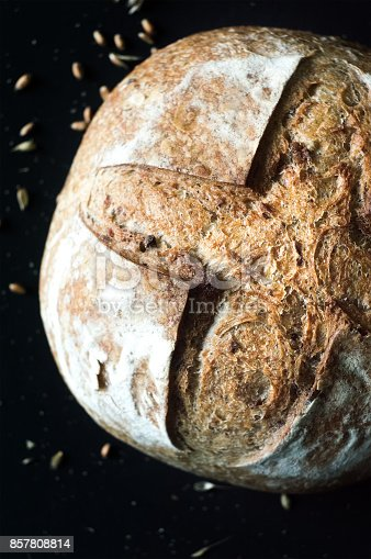 istock Close-up of crusty artisan bread with olives on black background, top view 857808814