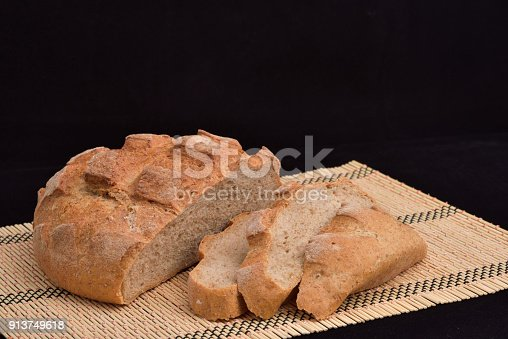 913749618istockphoto Close-up of crusty garlic bread on wooden background 913749618