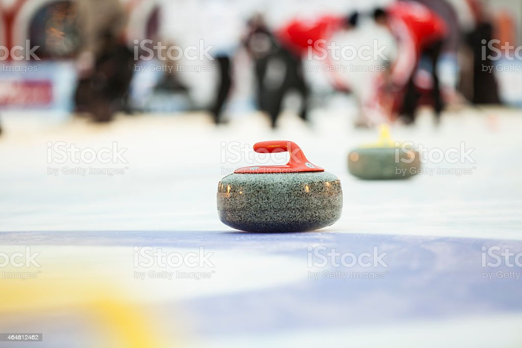 Close-up of curling stone with team out of focus​​​ foto