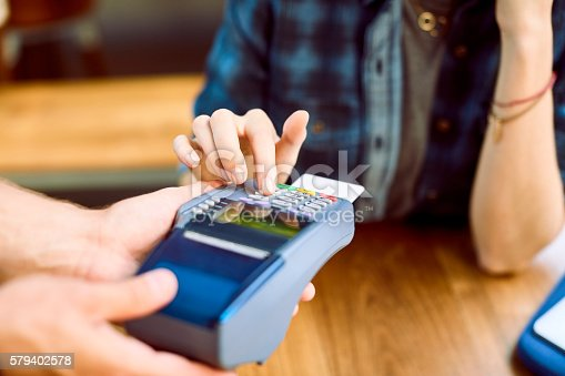 istock Close-up of customer entering pin on card reader 579402578