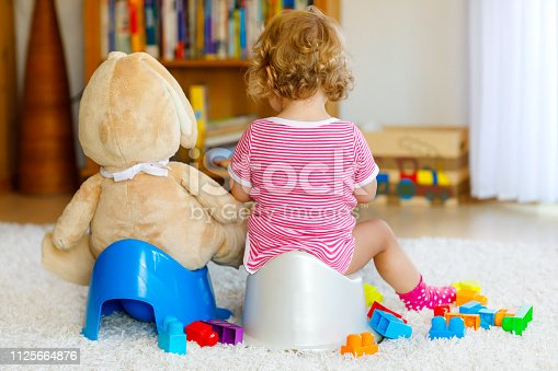istock Closeup of cute little 12 months old toddler baby girl child sitting on potty. Kid playing with big plush soft toy. Toilet training concept. Baby learning, development steps 1125664876