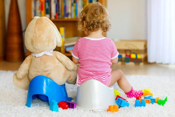 Nahaufnahme der niedliche kleine 12 Monate alt Kleinkind Baby Mädchen sitzen auf dem Töpfchen. Kind spielt mit großer Plüsch Stofftier. Toilettentraining Konzept. Baby Entwicklung Lernschritte – Foto