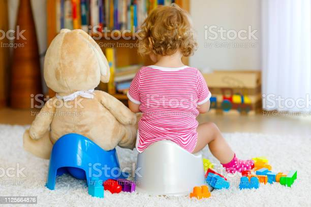 Little girl sitting on potty with toilet paper — Stock