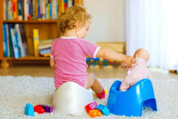 Nahaufnahme von niedlichen kleinen 12 Monate alten Kleinkind Baby Mädchen Kind sitzt auf Töpfchen. Kind spielt mit Puppenspielzeug. Toilettentrainingskonzept. Babylernen, Entwicklungsschritte – Foto