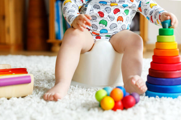 Closeup of cute little 12 months old toddler baby girl child sitting on potty. stock photo