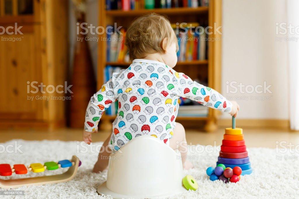 Closeup de lindo 12 meses de edad niño bebé niña niño pequeño sentado en la bacinica. - foto de stock