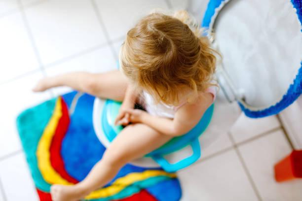 Nahaufnahme von niedlichen kleinen Kleinkind Baby Mädchen Kind sitzt auf toilette WC Sitz. Töpfchentraining für kleine Kinder. Unerkennbares Gesicht des Kindes – Foto
