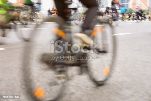 istock Close-up of cyclists on the bicycle, the cyclist's foot on the pedals, the marathon on the streets. Abstract blurred sport background 863454090