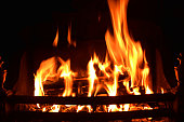 Closeup of dancing flames of burning wooden logs in fireplace, warming light in Christmas holidays