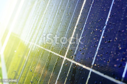 Close-up of dark blue solar panel with water drops and reflection of green trees and house on the background of grass and blue sky. Image with shallow depth of field. Toned with sunshine.