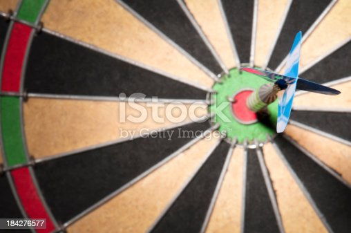 A single blue dart in a bulls eye on a dartboard. The dark is embedded in the small red circle which marks the centre of the dartboard know as the bulls eye. The focus is on the blue end of the dart. The dartboard has a chequered pattern across it in black and white with red and green sections marking the edges of the board.