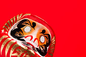 close-up of daruma doll on red background