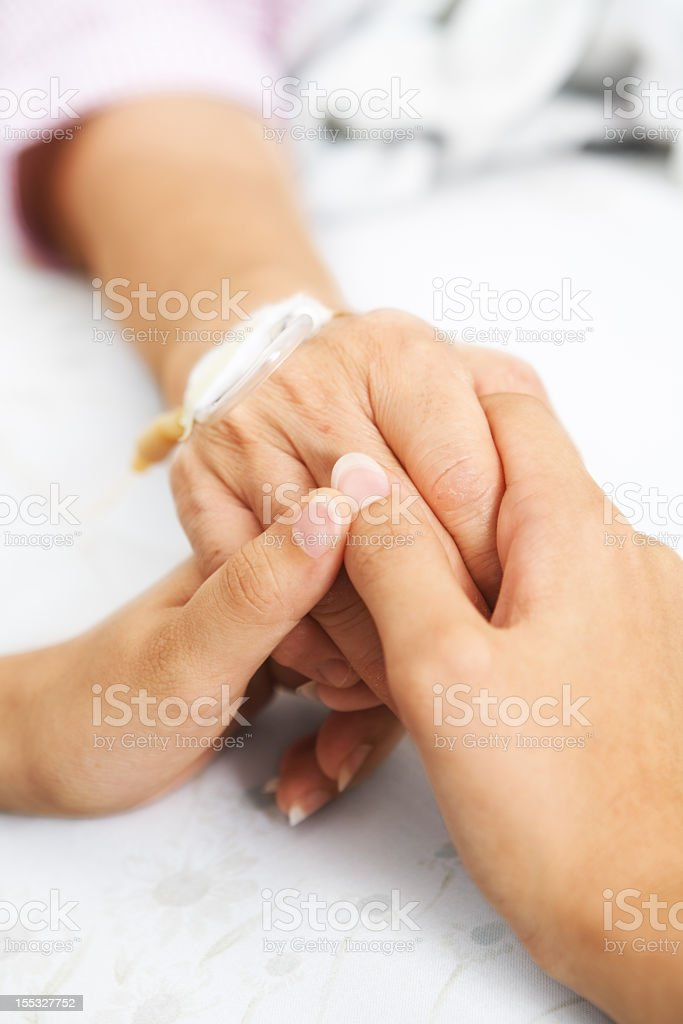 Close-up of daughter holding mother's hand in the hospital stock photo