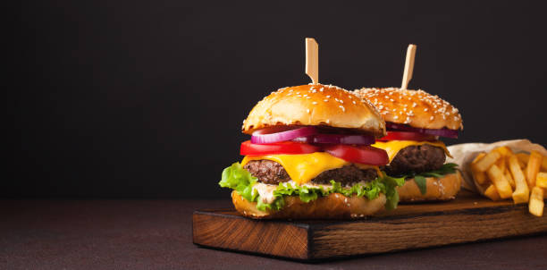 Close-up of delicious fresh home made burger with lettuce, cheese, onion and tomato on a dark background with copy space. fast food and junk food concept stock photo