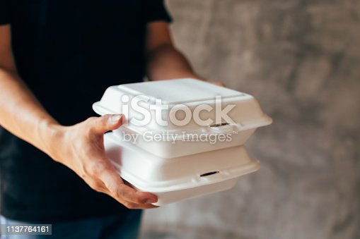 Close-up of delivery man handing a slack of foam lunch box - Foam box is toxic plastic waste. It can be used for recycling and environment saving concept
