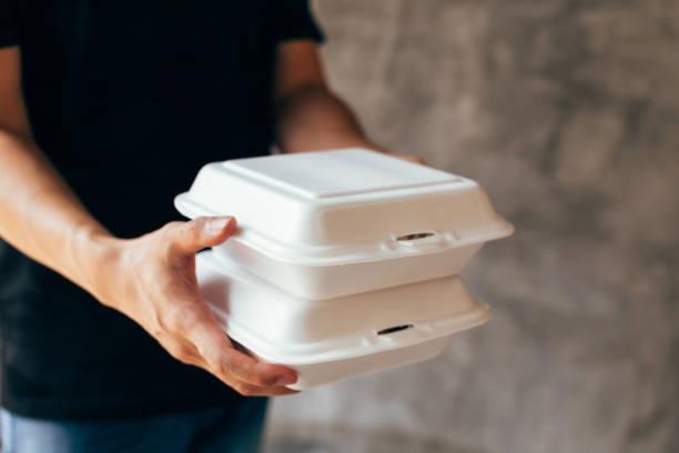 close-up do homem de entrega que distribui um slack da caixa de almoço da espuma - recipiente - fotografias e filmes do acervo