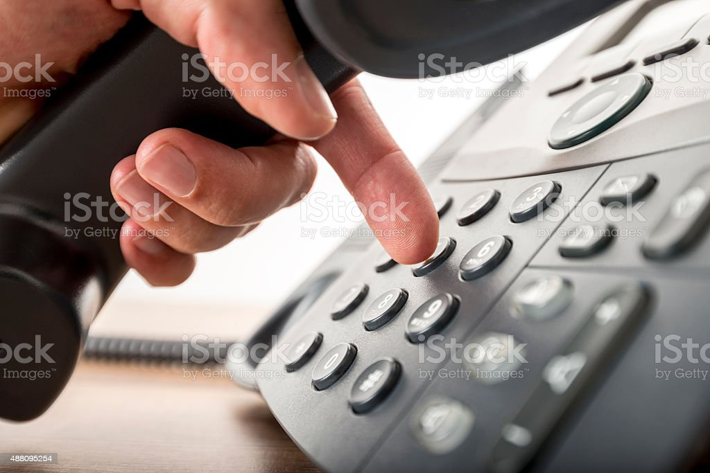 Closeup of dialing a telephone number stock photo