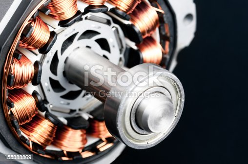 Detail of copper winding, stack and shaft of a  electric permanent magnet motor for home appliances. Selective focus and black background.