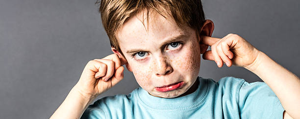 closeup of displeased little boy with freckles against education problems closeup of displeased little boy with red hair and freckles ignoring parents scolding, blocking his ears with fingers against education problems, grey background hands covering ears stock pictures, royalty-free photos & images