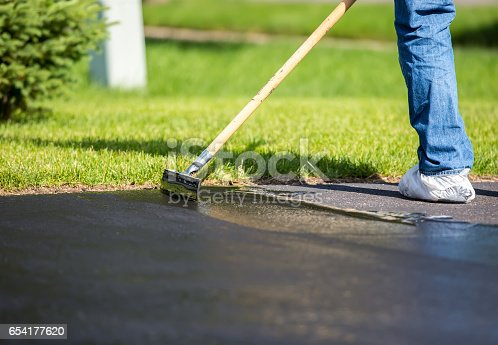 Close-up of a home owner seal coating their driveway. They are using a