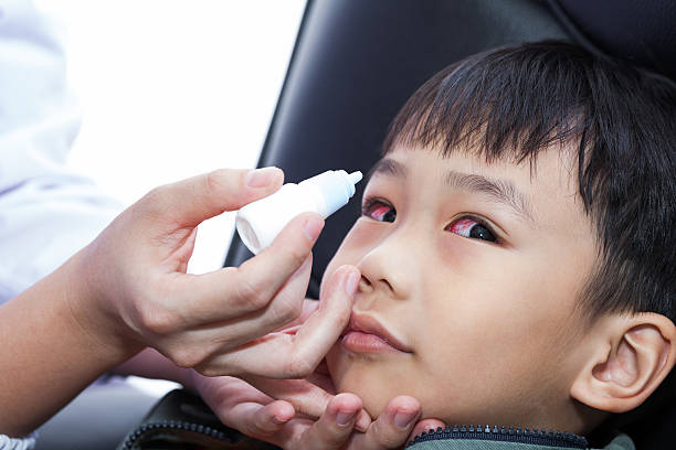 Closeup of doctor pouring eye drops in eye patient stock photo