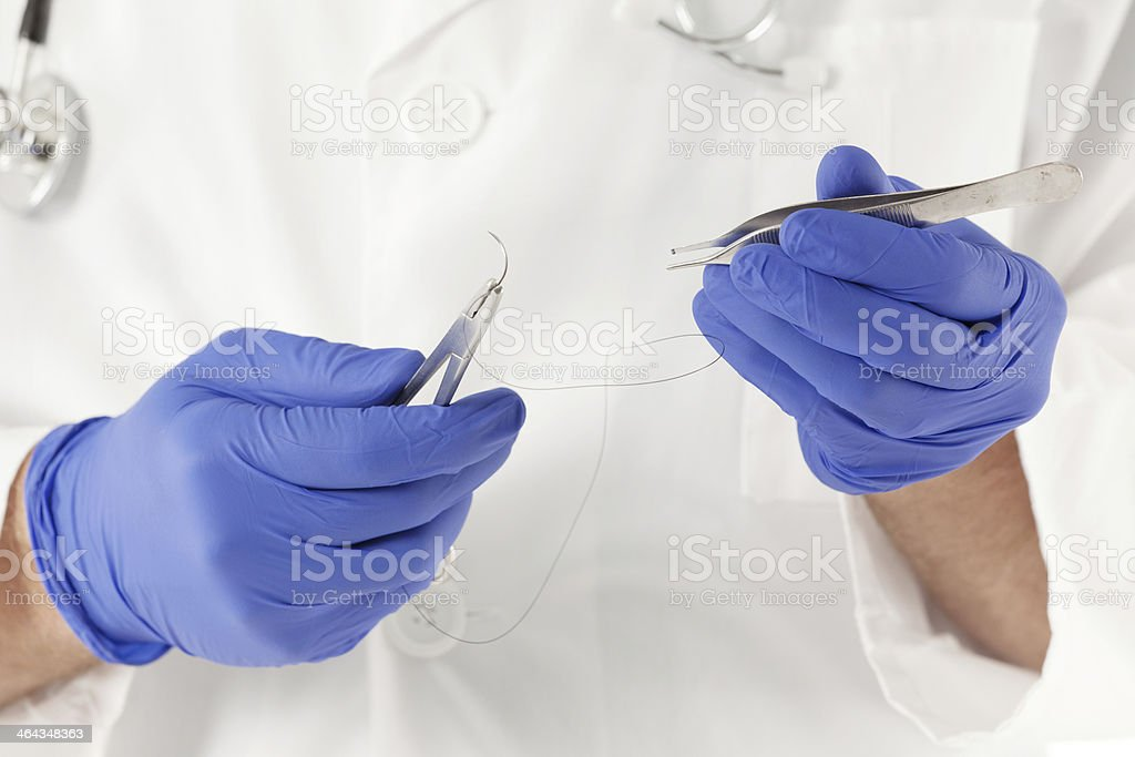 Close-up of doctor's hands with surgical instruments royalty-free stock photo
