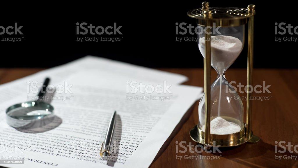 Close-up van het document en de zandloper op tafel, contract periode die afloopt geldigheid foto