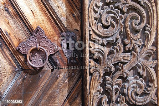 Close-up of door and carved decoration on an old wooden shed in Norway. Photo was taken near Lillesand in the southern part of Norway