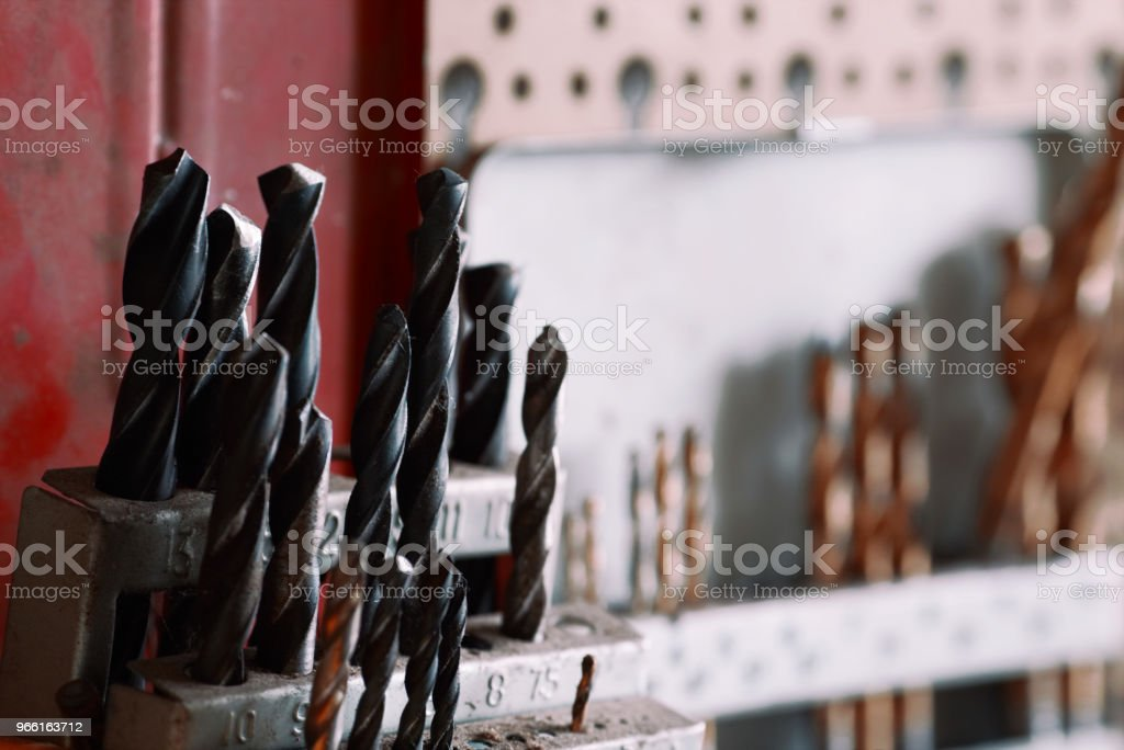 Close-up of drill bit set in a holder at workshop .Set of drills hanging on a wall. - Royalty-free Black Color Stock Photo