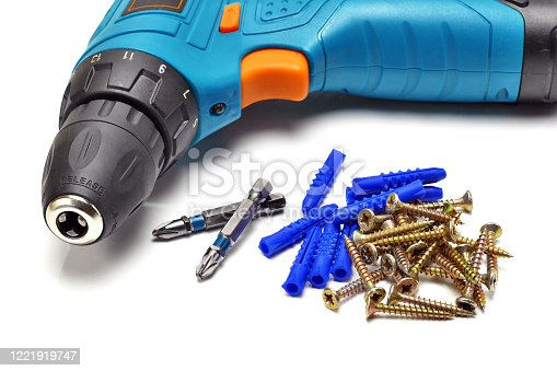 closeup of drill machine, bits, dowels and screws on white background