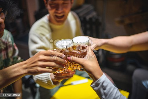 High angle close-up of four friends raising glasses in celebratory toast at table outside Tokyo izakaya.