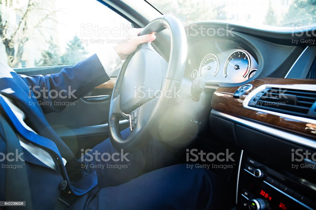 Close-up of driver sitting in the car behind the wheel stock photo