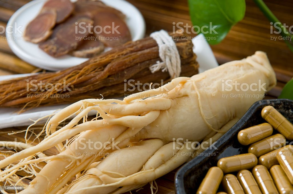 Close-up of dry ginseng slices, capsules and roots stock photo