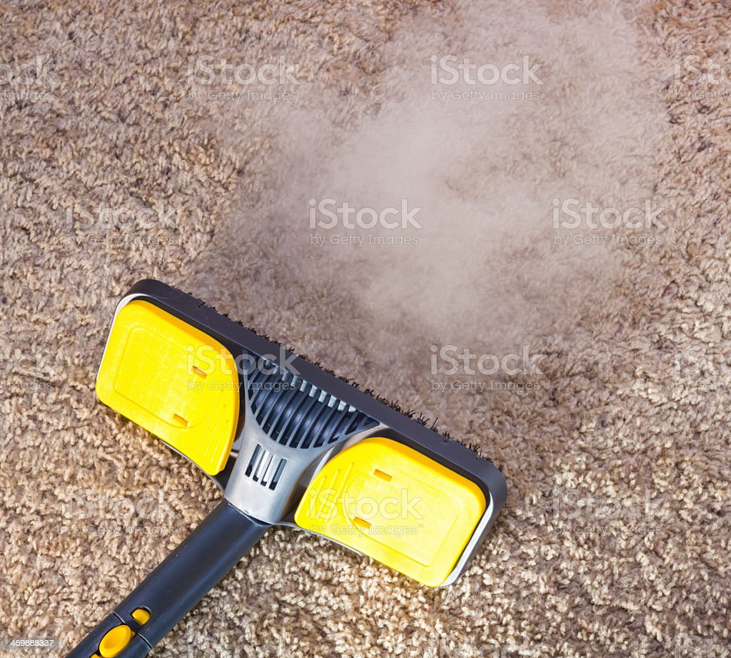 Close-up of dry steam cleaner cleaning a carpet stock photo