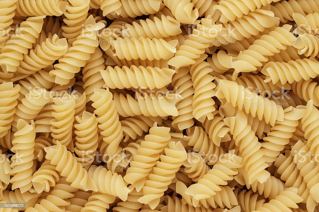close-up of dry uncooked rotini texture background stock photo