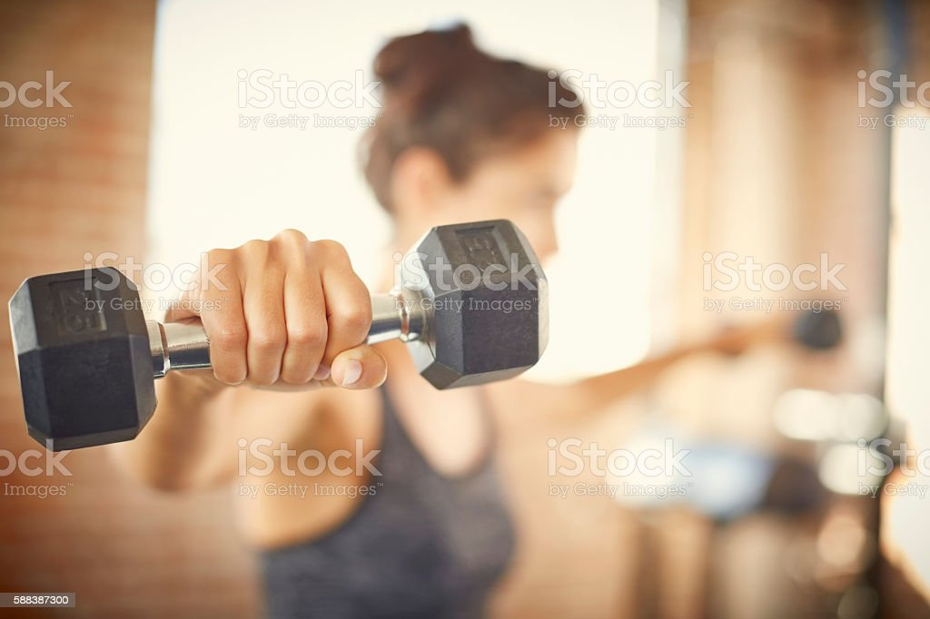 Close-up of dumbbell held by young woman in gym stock photo