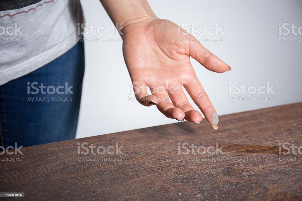 Close-up of dust on woman finger Close-up of dust on woman finger taken from wooden table 2015 Stock Photo