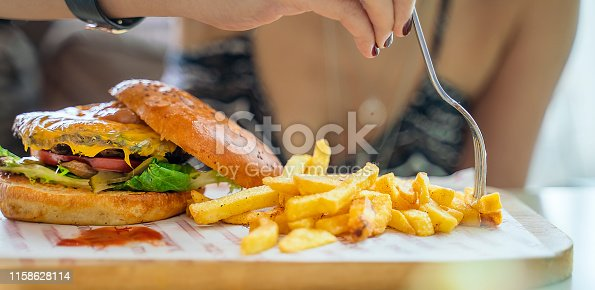 Close-up of eating cheeseburger with French fries chips