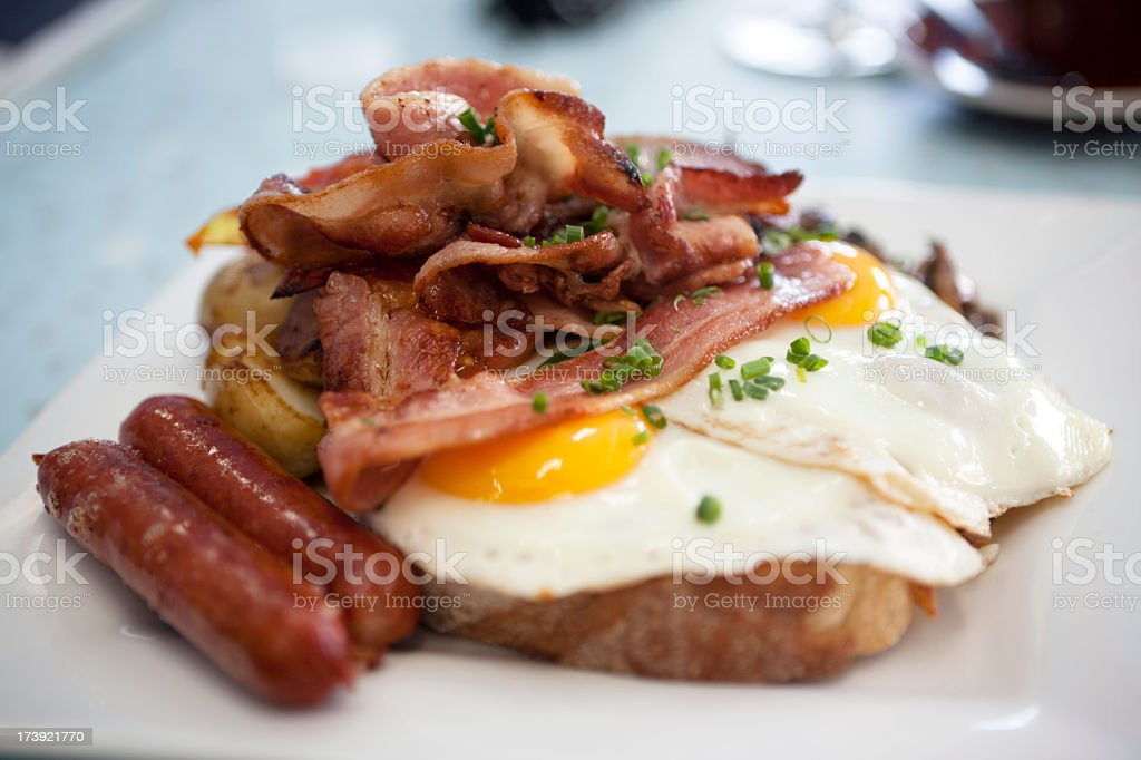A closeup of eggs, bacon, ham, and sausage on top of toast stock photo