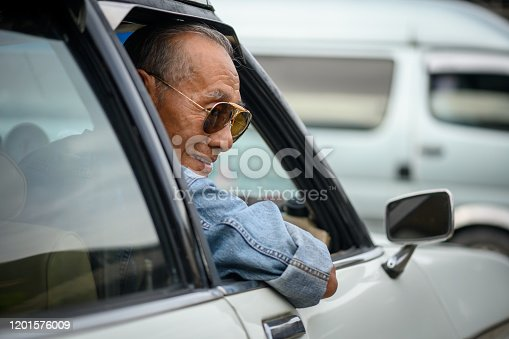 Image of Closeup of Elderly Asian man with stylish sunglasses drive a car.