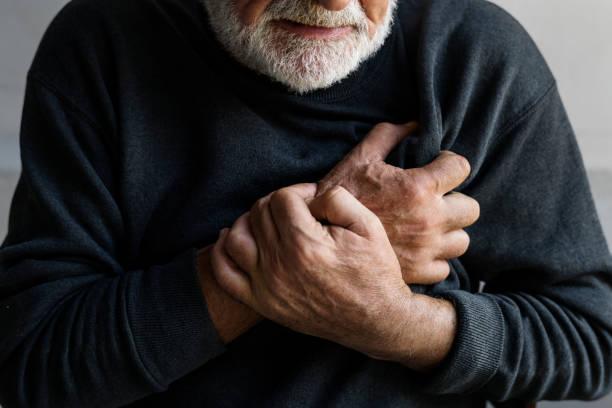 Close-up do homem idoso com dor no peito de ataque cardíaco - foto de acervo