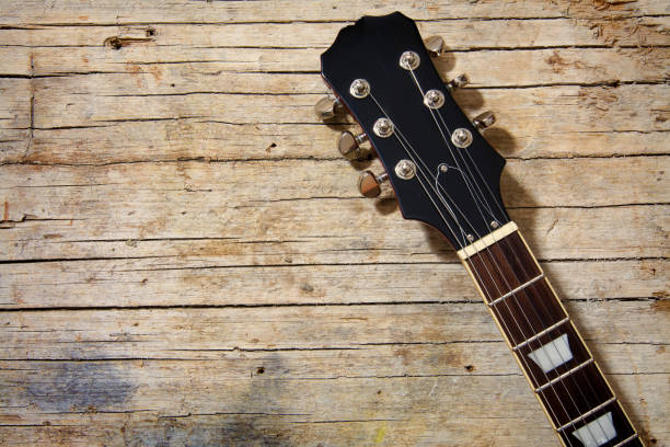 Close-up of electric guitar lying on vintage wood background, with copy space Close-up of electric guitar lying on vintage wood background, with copy space country and western music stock pictures, royalty-free photos & images