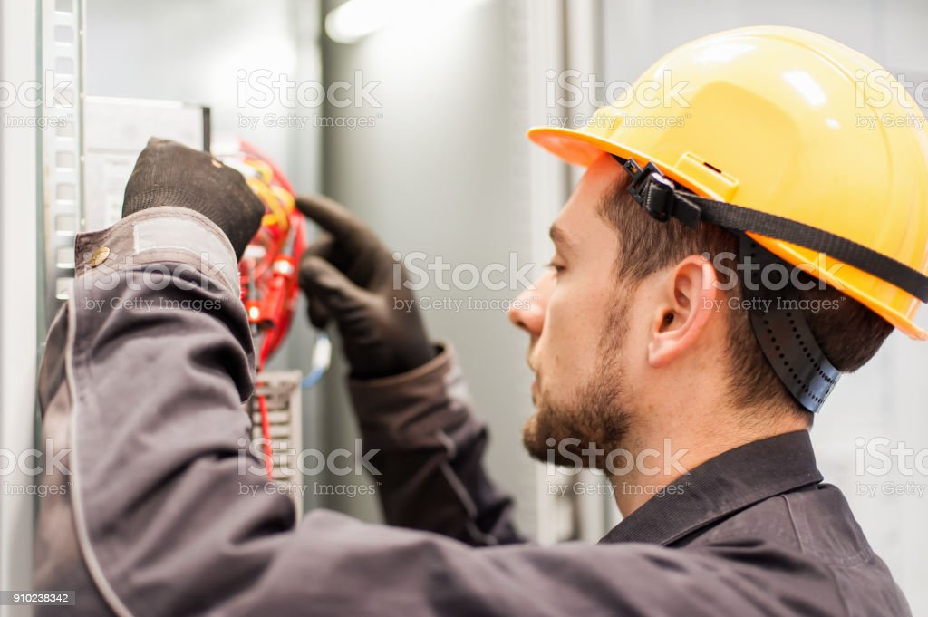 Closeup of electrician engineer works with electric cable wires stock photo