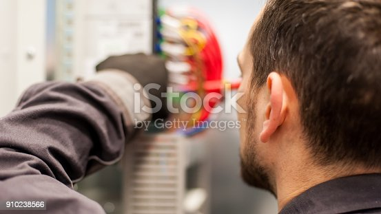 istock Closeup of electrician engineer works with electric cable wires 910238566