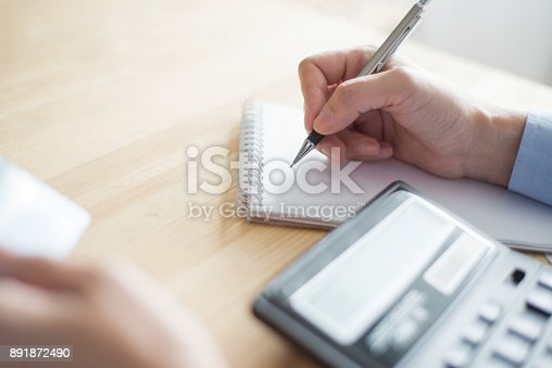 645670208istockphoto Closeup of Employee making Notes 891872490
