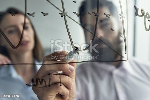 Close-up shot through glass of man drawing scheme on glass surface with woman in colleague standing near