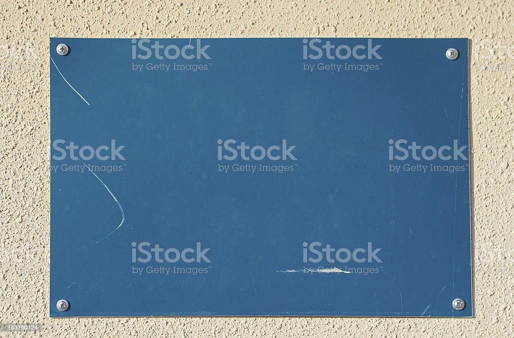 Closeup of empty blue board on beige concrete wall stock photo
